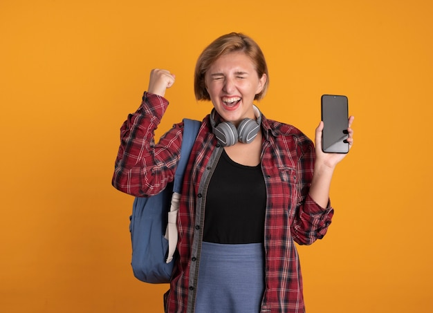 Aufgeregtes junges slawisches studentenmädchen mit kopfhörern, das rucksack trägt, steht mit geschlossenen augen und hebt die faust, die das telefon hält