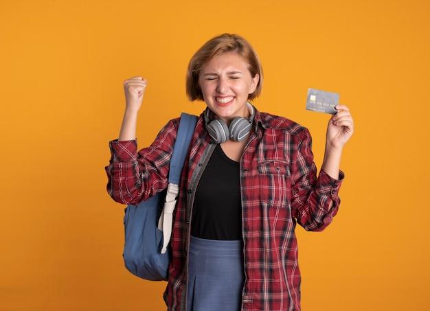 Aufgeregtes junges slawisches studentenmädchen mit kopfhörern, das rucksack trägt, steht mit geschlossenen augen und hebt die faust mit kreditkarte credit