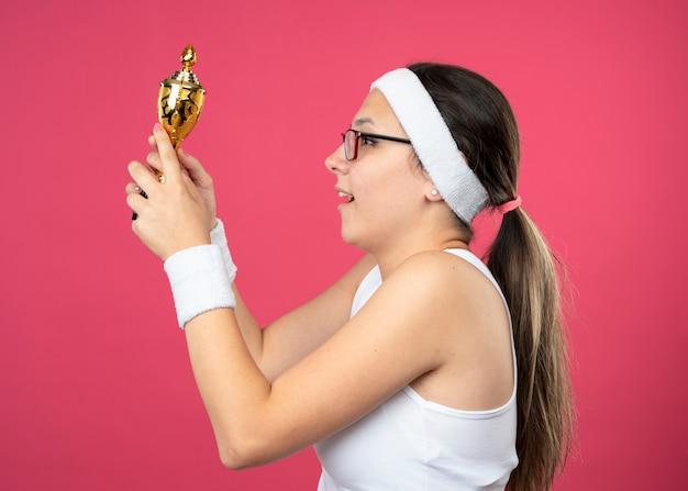 Aufgeregtes junges sportliches mädchen in optischer brille mit stirnband und armbändern steht seitlich und hält den siegerpokal