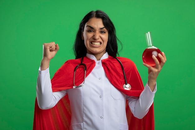 Aufgeregtes junges superheldenmädchen, das medizinische robe mit stethoskop hält, die chemieglasflasche gefüllt mit roter flüssigkeit zeigt, die ja geste lokalisiert auf grüner wand zeigt
