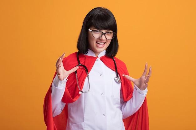 Aufgeregtes junges superheldenmädchen, das stethoskop mit medizinischem gewand und umhang mit brille trägt, die hände ausbreitet