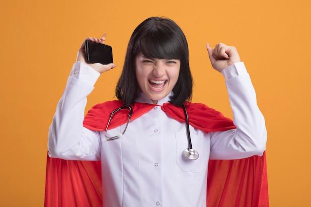 Aufgeregtes junges superheldenmädchen, das stethoskop mit medizinischem gewand und umhang trägt telefon hält und hände hebt