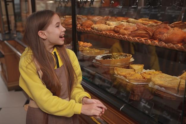 Aufgeregtes kleines bäcker-mädchen, das fröhlich bäckerei-einzelhandelsanzeige untersucht