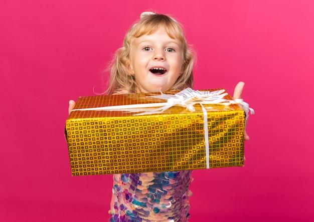 Aufgeregtes kleines blondes mädchen, das geschenkbox isoliert auf rosa wand mit kopienraum hält