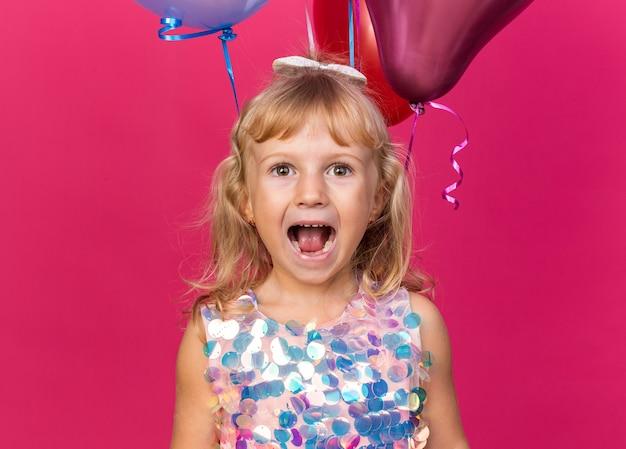 Aufgeregtes kleines blondes mädchen, das mit heliumballons steht, isoliert auf rosa wand mit kopierraum