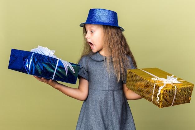 Aufgeregtes kleines blondes mädchen mit blauem partyhut, das geschenkboxen auf olivgrüner wand mit kopienraum isoliert hält und betrachtet