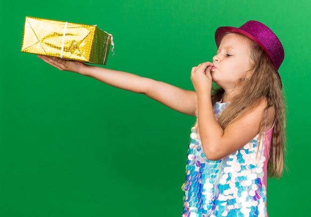 Aufgeregtes kleines blondes mädchen mit lila partyhut, das geschenkbox hält und ihre finger einzeln auf grüner wand mit kopienraum küsst