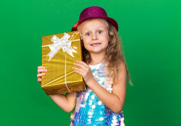 Aufgeregtes kleines blondes mädchen mit lila partyhut, das geschenkbox isoliert auf grüner wand mit kopienraum hält