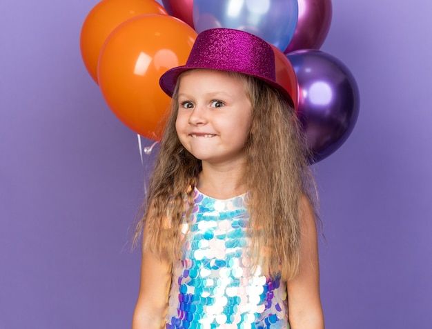 Aufgeregtes kleines blondes mädchen mit violettem partyhut, das mit heliumballons steht, lokalisiert auf lila wand mit kopienraum