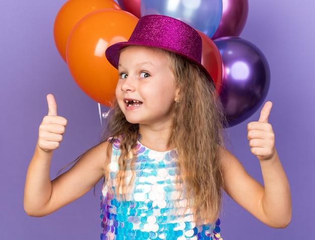 Aufgeregtes kleines blondes mädchen mit violettem partyhut, das vor heliumballons steht, isoliert auf lila wand mit kopierraum