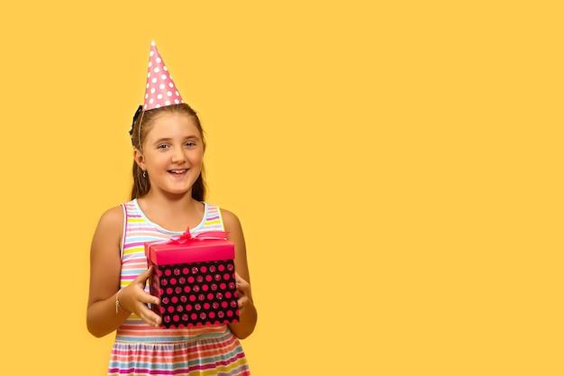 Aufgeregtes kleines kind, das geschenkbox hält und vor freude lächelt