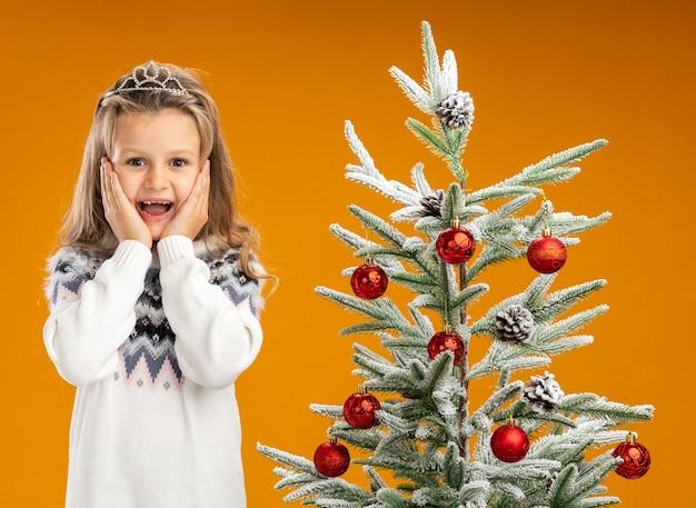 Aufgeregtes kleines mädchen, das nahe weihnachtsbaum steht, der tiara mit girlande am hals trägt, die hände auf wangen lokalisiert auf orange hintergrund setzt
