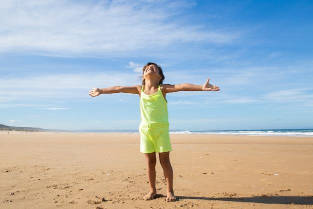 Aufgeregtes kleines mädchen, das sommerkleidung trägt, mit fliegenden händen am strand steht und sich nach oben dreht