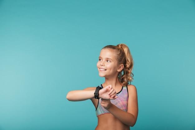 Aufgeregtes kleines mädchen, das sportkleidung unter verwendung der intelligenten uhr trägt, die über blauer wand isoliert wird