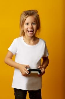 Aufgeregtes kleines mädchen, das videospiel spielt
