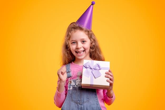 Aufgeregtes kleines mädchen im partyhut, das verpackte geschenkbox zeigt, während geburtstag vor hellgelbem hintergrund feiert