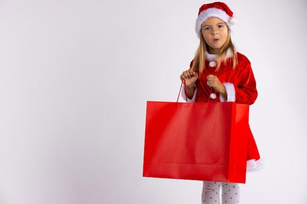 Aufgeregtes kleines mädchen überrascht von geschenk in der einkaufstasche gefunden, sieht emotional aus. weihnachtskind auf winterverkauf, lokalisiert auf weißer wand mit leerem raum.