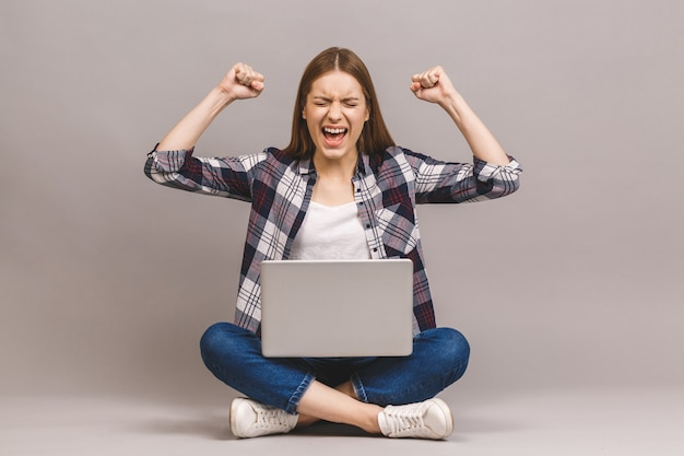 Aufgeregtes lächelndes mädchen, das mit laptop auf dem boden sitzt und eine hand in die luft hebt, gewinnt sie