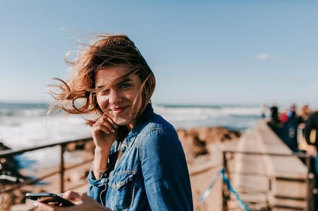 Aufgeregtes liebenswertes modell, das fotoshooting im freien mit lächeln genießt glückliche frau, die musik am ufer des ozeans hört und aufwirft