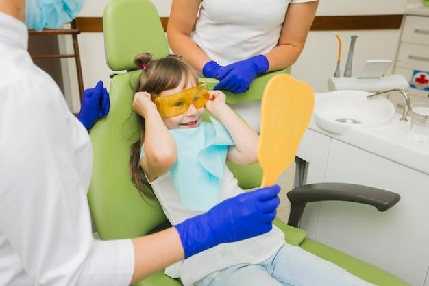 Aufgeregtes mädchen am zahnarzt, der spiegel betrachtet