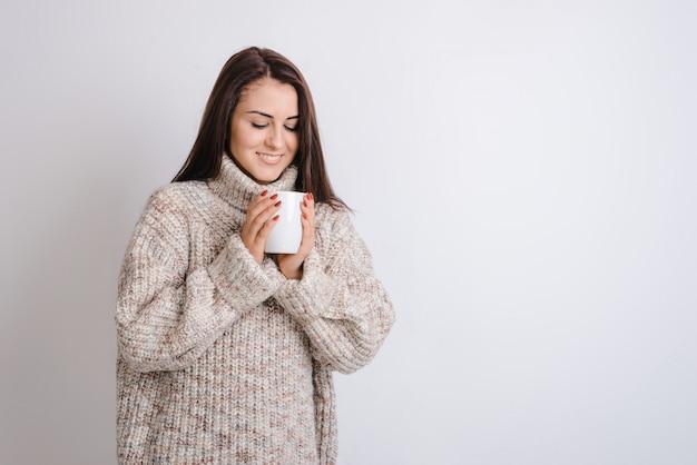 Aufgeregtes mädchen, das heißen tee, tragende warme strickjacke auf grauem hintergrund genießt