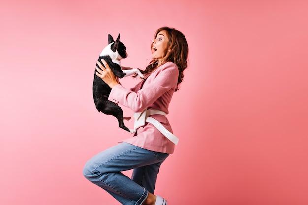 Aufgeregtes mädchen, das mit französischer bulldogge tanzt. porträt der prächtigen dame, die hund mit überraschtem lächeln betrachtet.