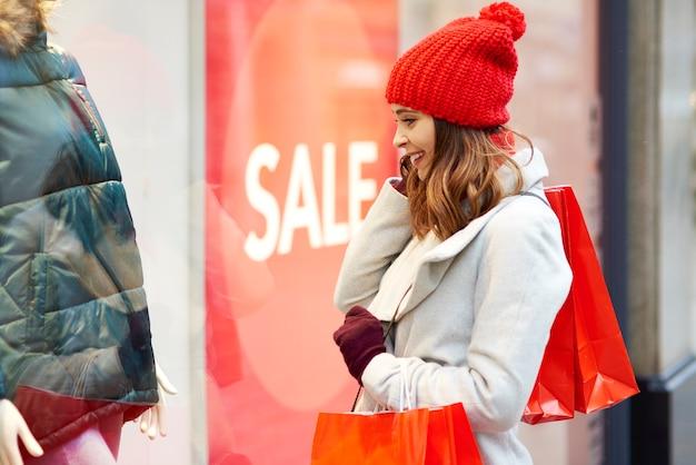 Aufgeregtes mädchen, das schaufenster während des wintereinkaufs betrachtet