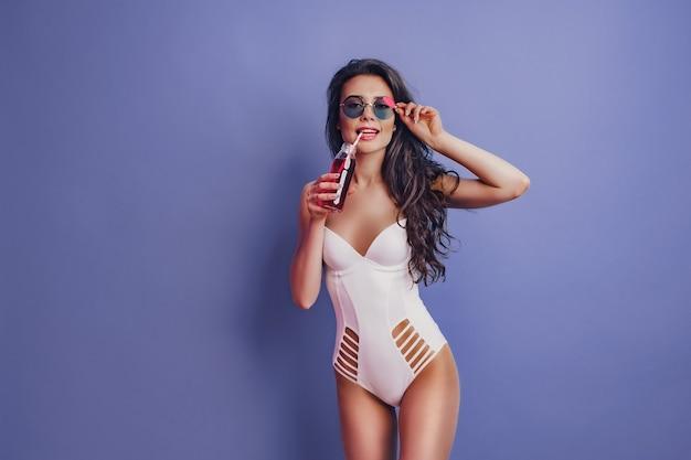 Aufgeregtes mädchen der jungen frau im weißen einteiligen badeanzug, sonnenbrille, die mit getränk auf lila hintergrund lokalisiert aufwirft.