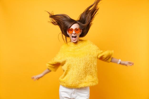 Aufgeregtes mädchen in pelzpullover und herzorangefarbener brille, die im studio springen, mit fliegenden haaren einzeln auf hellgelbem hintergrund. menschen aufrichtige emotionen, lifestyle-konzept. werbefläche.