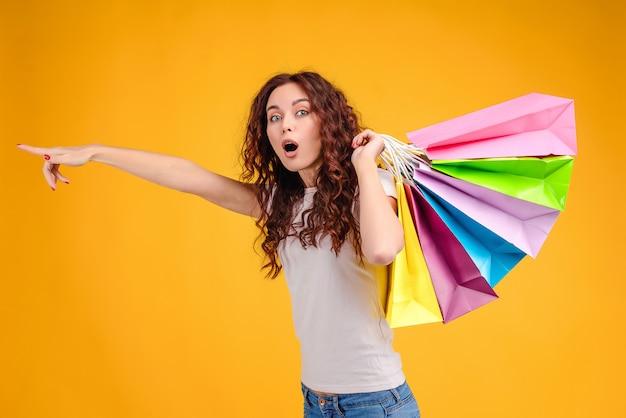 Aufgeregtes mädchen mit bunten einkaufstaschen vorwärts zeigend lokalisiert über gelb