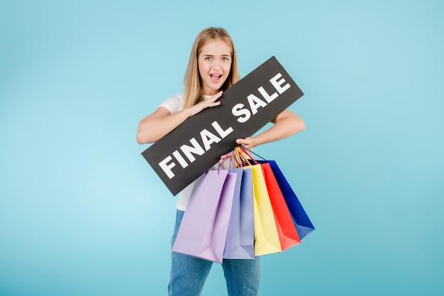 Aufgeregtes mädchen mit dem abschließenden verkaufszeichen und bunten einkaufenbeuteln getrennt über blau