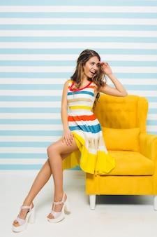 Aufgeregtes mädchen mit der schönen frisur, die weg schaut und auf modernen gelben möbeln auf gestreifter wand sitzt. porträt der verträumten jungen frau im hellen trendigen kleid, das haar mit ihrer hand berührt.