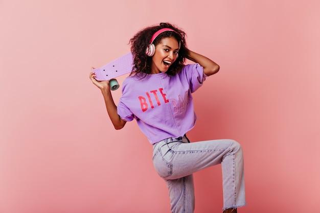 Aufgeregtes mädchen mit dunklem haar, das mit skateboard tanzt. anmutige afrikanische junge dame in jeans, die musik hört und herumalbern.