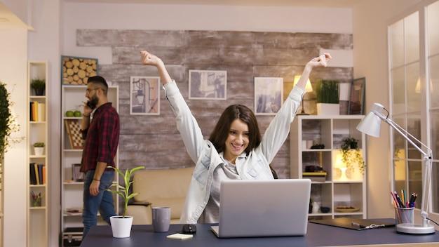 Aufgeregtes mädchen mit erhobenen händen beim arbeiten am laptop im wohnzimmer. zeitlupenaufnahmen