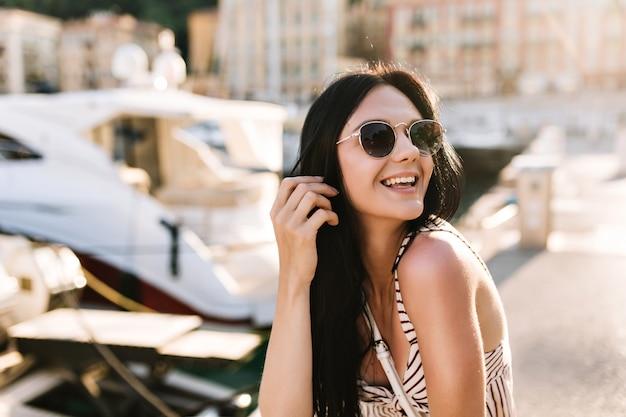 Aufgeregtes mädchen mit langen schwarzen haaren, die glücklich lachen, während sie draußen mit booten sitzen