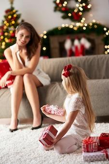 Aufgeregtes mädchen öffnet ihre weihnachtsgeschenke
