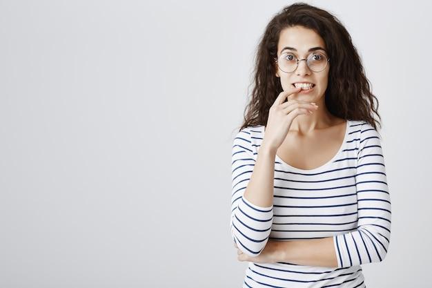 Aufgeregtes neugieriges mädchen in der brille, das finger beißt und interessiert schaut