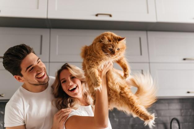 Aufgeregtes paar, das mit flauschiger katze aufwirft. innenporträt der lächelnden entzückenden frau, die ihr haustier in der küche hält.