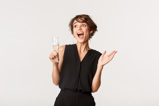 Aufgeregtes partygirl, das freudige obere linke ecke schaut, glas champagner hält und über weiß steht.