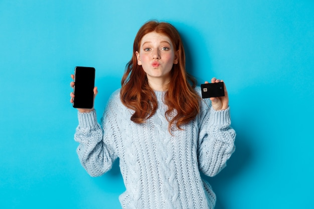 Aufgeregtes rothaariges mädchen, das handybildschirm und kreditkarte zeigt, online-shop oder anwendung demonstrierend, über blauem hintergrund stehend.