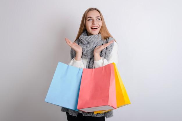 Aufgeregtes schönes mädchen, das die warme strickjacke und schal halten einkaufstaschen lokalisiert über grauem hintergrund trägt