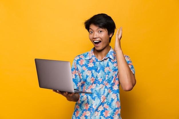 Aufgeregtes schreien schockierte jungen asiatischen mann, der isoliert über gelbem raum unter verwendung des laptops steht.