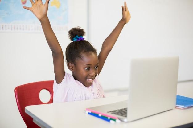 Aufgeregtes schulmädchen mit laptop im klassenzimmer