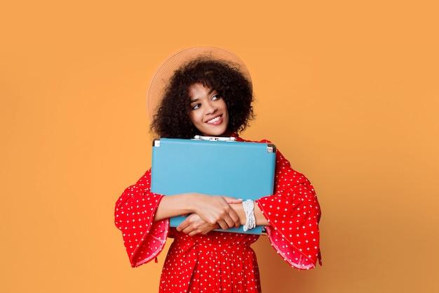 Aufgeregtes schwarzes mädchen mit afrikanischer frisur, die niedlichen blauen koffer hält.