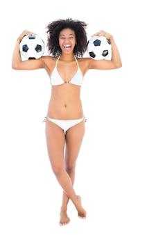 Aufgeregtes sitzmädchen im weißen bikini, der fußball hält