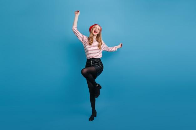 Aufgeregtes stilvolles mädchen, das auf blauer wand tanzt. ansicht der angenehmen blonden dame im schwarzen rock in voller länge.