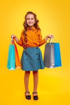 Aufgeregtes stilvolles mädchen, das einkaufstaschen trägt