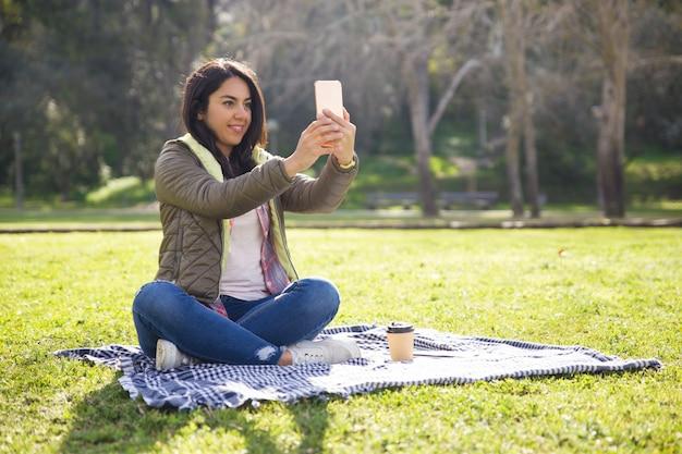 Aufgeregtes studentenmädchen, das im park stillsteht und selfies nimmt