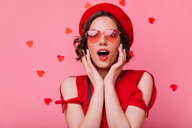 Aufgeregtes süßes mädchen, das mit offenem mund aufwirft. innenaufnahme der brünetten dame in der roten baskenmütze.
