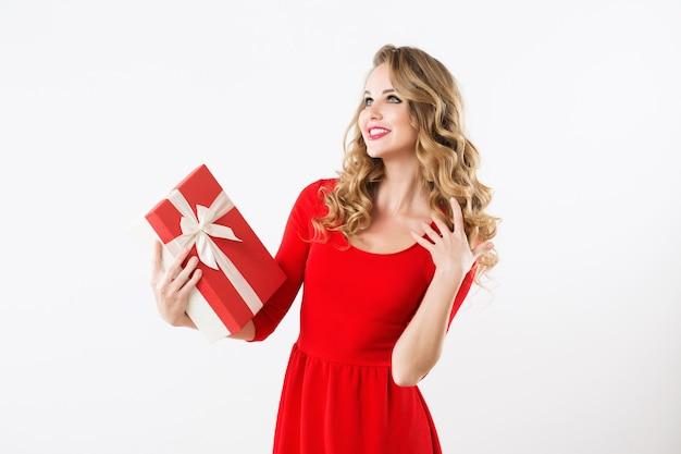 Aufgeregtes süßes mädchen im roten kleid, das geschenkbox hält